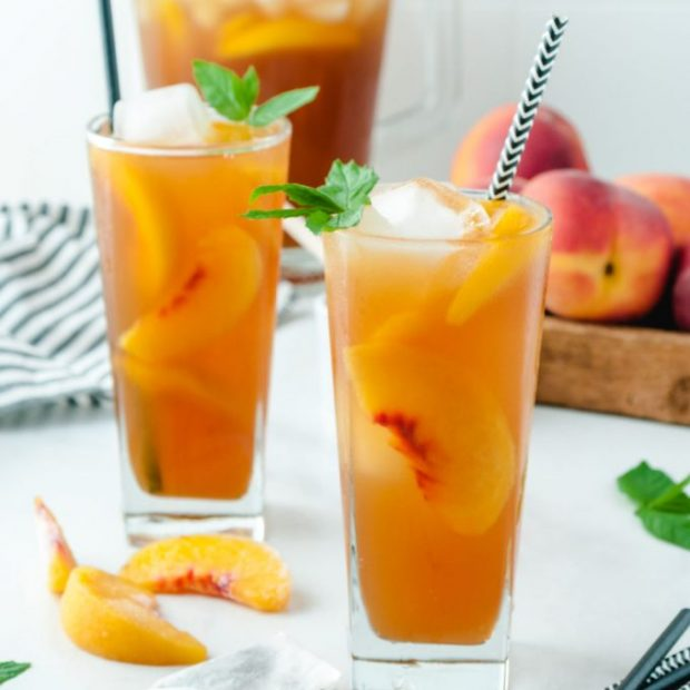 A close up of a glass of orange juice, with Iced tea