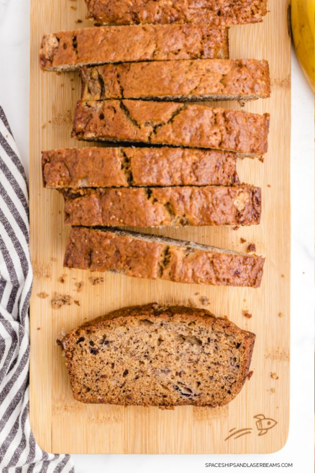 a loaf of banana bread sliced into pieces sitting on a wood cutting board