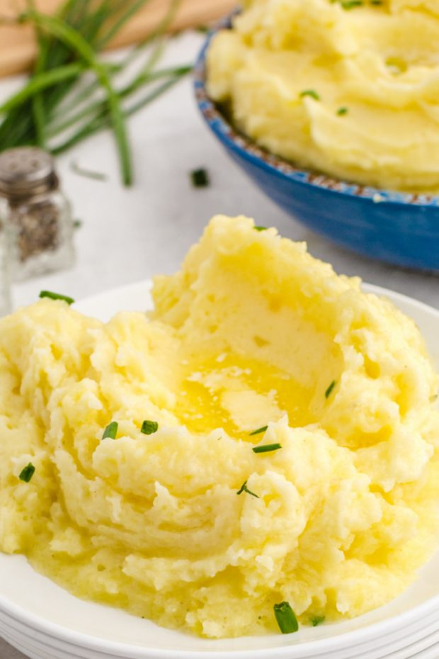plate of mashed potatoes with chives and pools of butter on a table about to be served