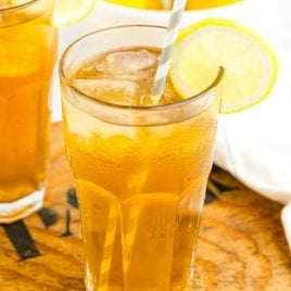 close up shot of glasses of iced tea served with lemon slices and straws