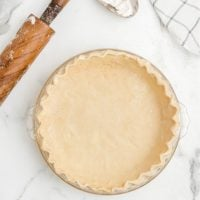 whole pie crust on marble surface with rolling pin