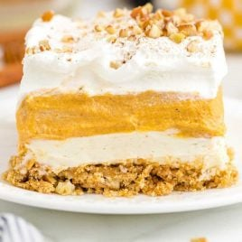 close up side shot of a slice of Pumpkin Delight topped with chopped pecans on a plate