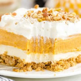 close up side shot of a slice of Pumpkin Delight topped with chopped pecans on a plate with a fork