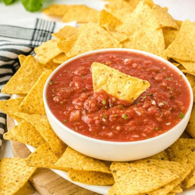 close up shot of a bowl of Salsa served with tortilla chips