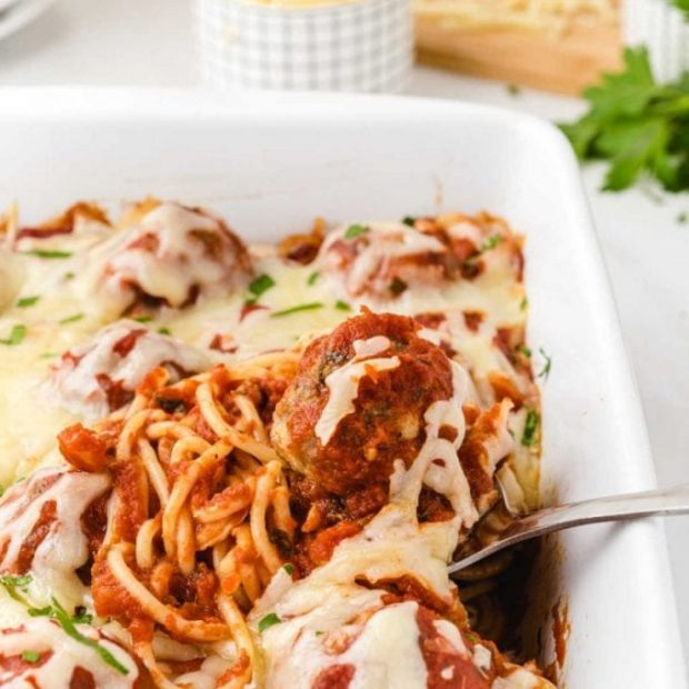 close up shot of baked spaghetti and meatballs in a baking dish