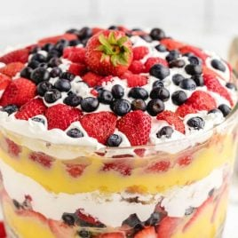 close up shot of vanilla trifle in a clear dish with strawberries and blackberries on top