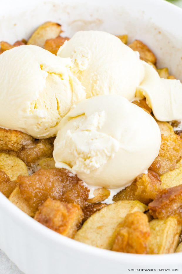 close up shot of grandma's apple betty in a white casserole pan with a 3 scoops of ice cream on the top