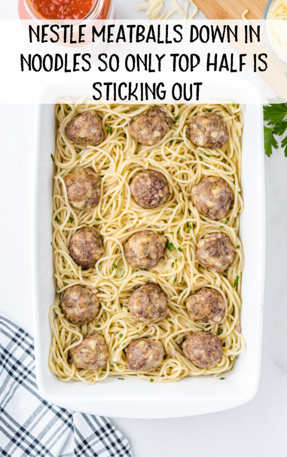 baked spaghetti and meatballs steps of placing meatballs in pasta in a white pan