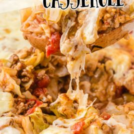 cabbage roll casserole in a clear baking dish being picked up by a wooden spoon