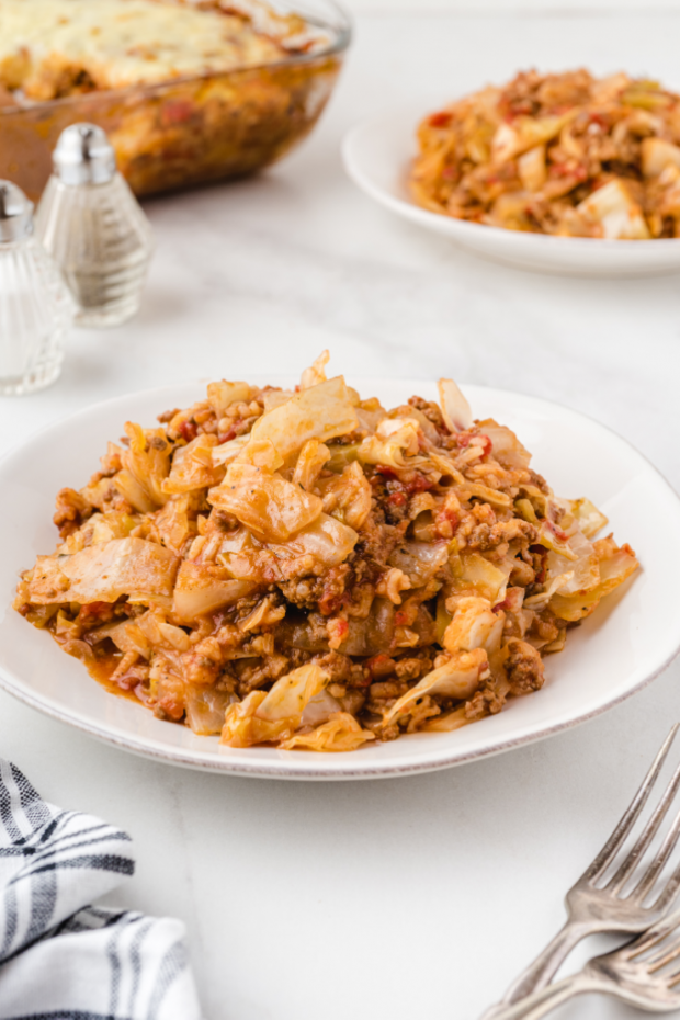 cabbage roll casserole on a white bowl with silver forks on the side on a white background