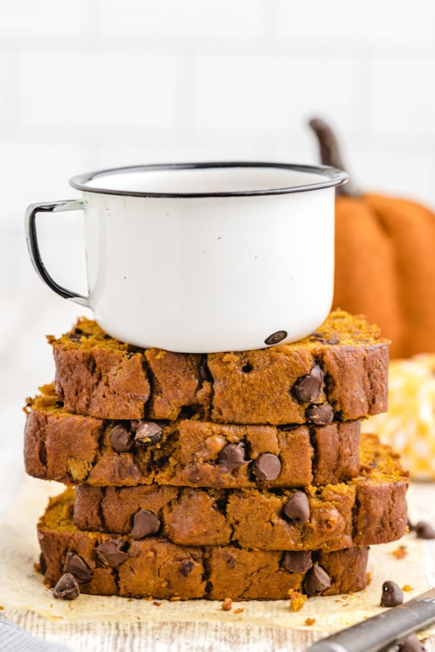 slices of chocolate chip pumpkin bread stacked on top of each other with a white mug on the top