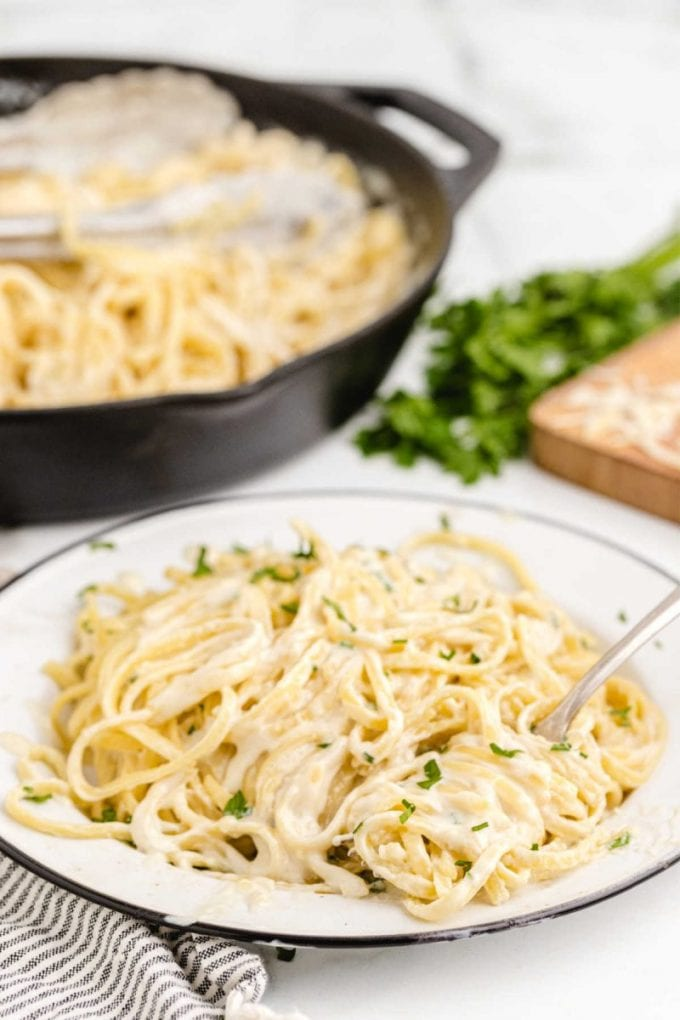 close up shot of a serving of Copycat Olive Garden Alfredo Sauce in a bowl with a fork