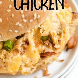 close up shot of crockpot crack chicken in a hamburger bun on a white plate