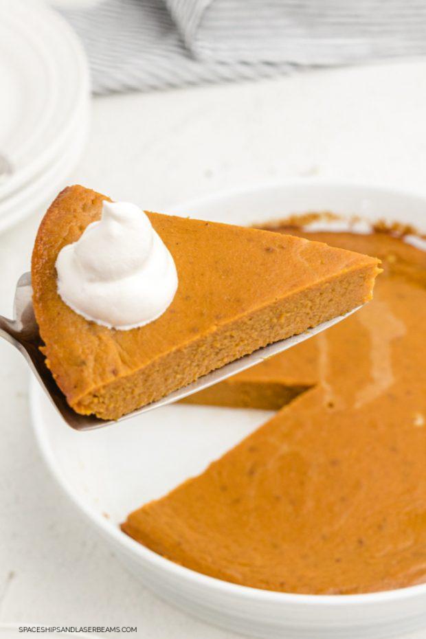 slice of crustless pumpkin pie being served from a pie dish