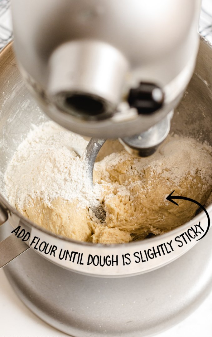 dinner rolls dough in a table mixer with flour added