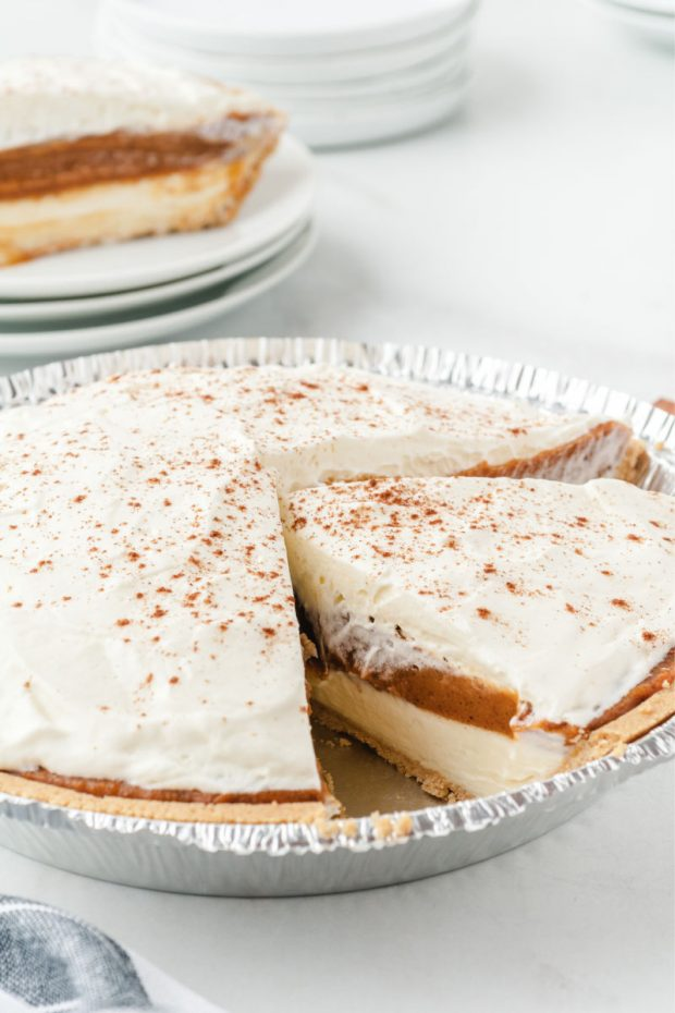 no bake pumpkin pie topped with whip cream and cinnamon in a aluminum pan with a piece cut