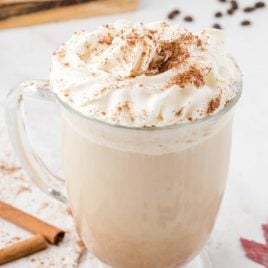 homemade pumpkin spice latte close up in glass mug on a table surface