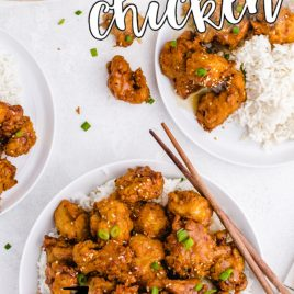 crispy honey chicken over rice on a white plate with chop stix on the side overhead shot