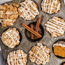 close up overhead shot of Pumpkin Spice Muffins drizzled with icing in a muffin pan