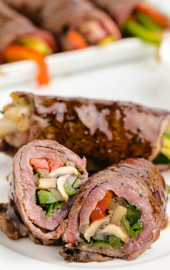 close up shot of balsamic glazed steak rolls stuffed with vegetables cut in half
