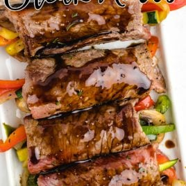 balsamic glazed steak rolls stuffed with vegetables on a tray