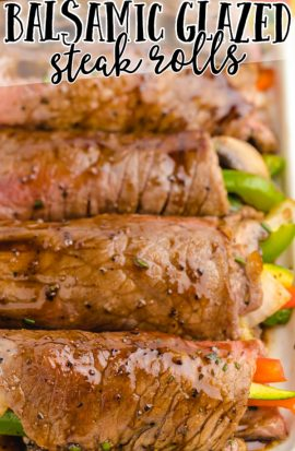 close up shot of balsamic glazed steak rolls stuffed with vegetables on a tray