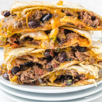 close up shot of sheet pan quesadillas stacked on top of each other on a white plate