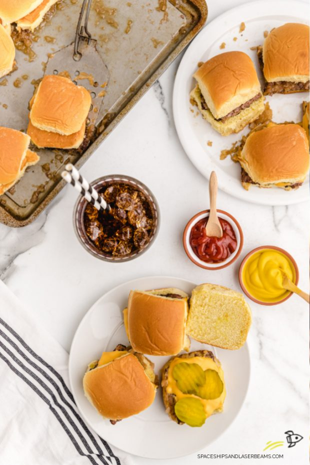 white castle sliders with pickles and cheese on white plate and a tin pan with ketchup, mustard, and a beverage