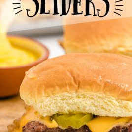 close up shot of white castle sliders with pickles and cheese on a wooden board