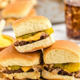 white castle sliders with pickles and cheese stacked on a wooden board