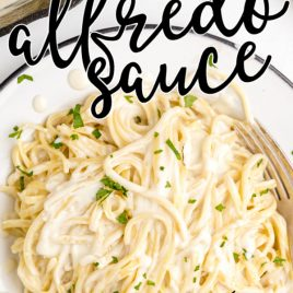 close up shot of copycat olive garden alfredo sauce topped over pasta and garnished with parsley in a white bowl