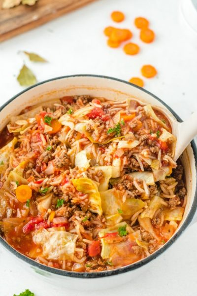 cabbage roll soup in a dutch oven with a spoon scooping out a serving