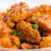 close up of crispy honey chicken in glass bowl
