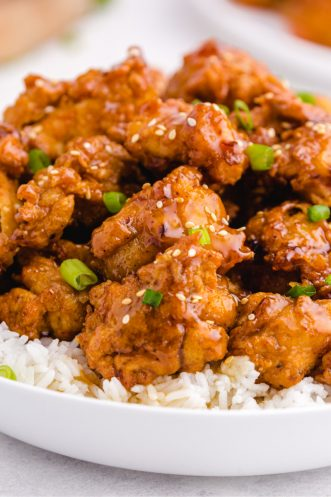 close up of crispy honey chicken over rice in white bowl