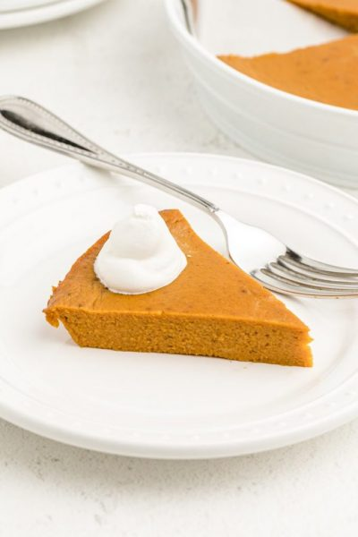 slice of crustless pumpkin with a dollop of cream on a white plate with a fork