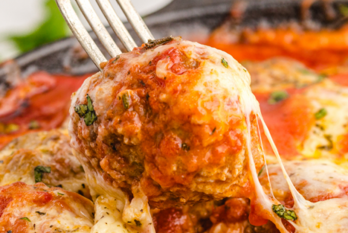 close up shot of meatball parmesan in a pan with parmesan cheese and pasta sauce on a fork
