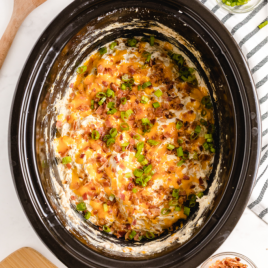 crockpot crack chicken in a crockpot topped with bacon bits, shredded chedder cheese, and green onions