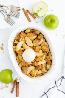 grandma's apple betty in a white casserole pan with a scoop of ice cream on top