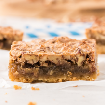 close up shot of pecan pie bars showing its inside layers on a white napkin