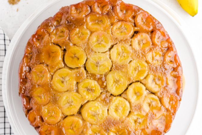 banana upside down cake served on a white tray with bananas and cinnamon on the side