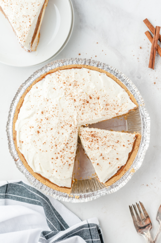 no bake pumpkin pie topped with whip cream and cinnamon in a aluminum pan