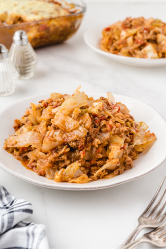 cabbage roll casserole in a white bowl with silver forks on the side on a white background