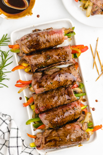 balsamic glazed steak rolls stuffed with vegetables on a white plate