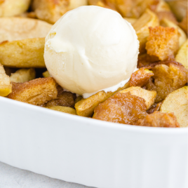 close up shot of grandma's apple betty in a white casserole pan with a scoop of ice cream on the top