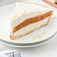 no bake pumpkin pie topped with whip cream and cinnamon on a white plate