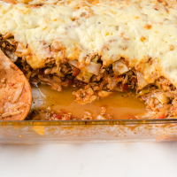 cabbage roll casserole in a clear baking dish with a wooden spoon
