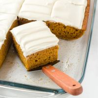 pumpkin bars with cream cheese frosting in a clear baking dish