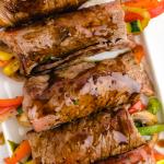 close up shot of balsamic glazed steak rolls stuffed with vegetables