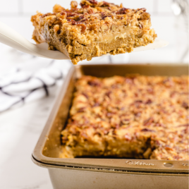 pumpkin crunch cake in a tin pan with a slice being picked up with a spatula