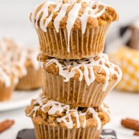 pumpkin spice muffins stacked on top of each other with white drizzled froting